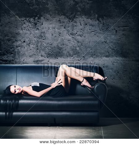 The beautiful woman lying on a leather sofa