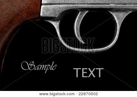 Extreme macro of vintage revolver trigger on black background with copy space.  Conceptual image for 'pulling the trigger' or initiating action.  (gun is replica of army  revolver from U.S. civil war)