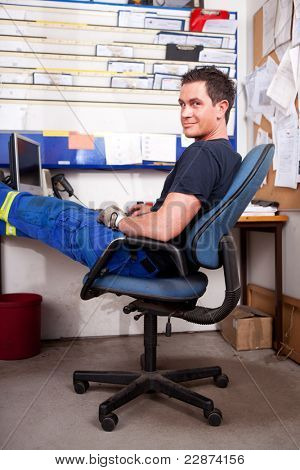 A relaxed auto mechanic leaning back in a chair in an office