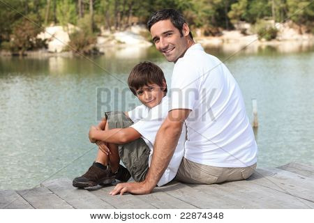 a father and his son seated on a pontoon faces a lake