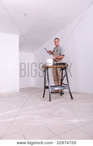 Decorator painting a room white