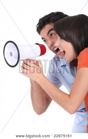 Young couple shouting into a loudspeaker