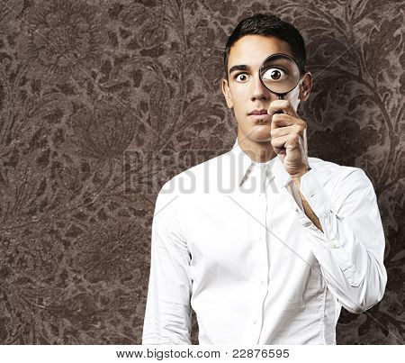 Portrait of handsome young man looking through a magnifying glass against a grunge wall