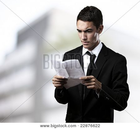 portrait of young business man reading contract in a house