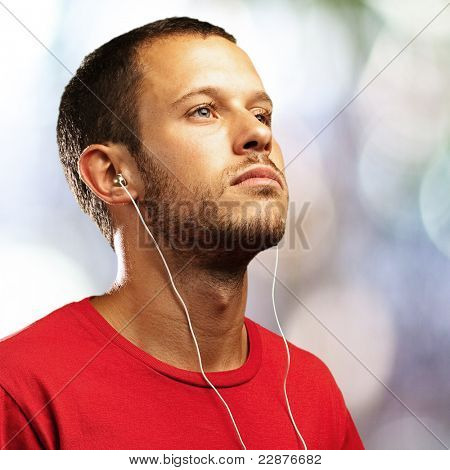 young man listening to music against a city lights background