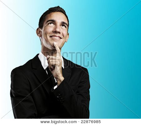 portrait of handsome young business man thinking and looking up against a blue background