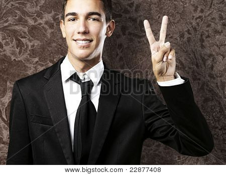 portrait of handsome young man doing peace symbol against a vintage background