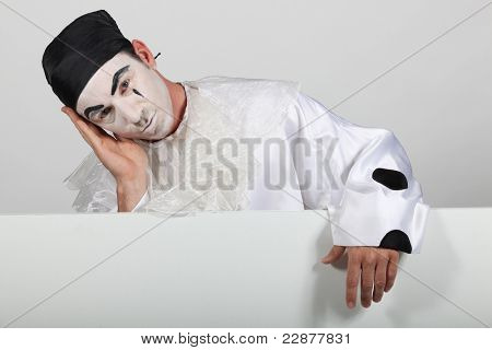 Man in Pierrot costume with a board ready for your text