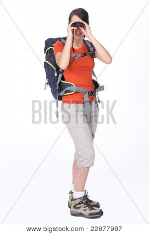 Studio shot of young woman rambler looking through binoculars