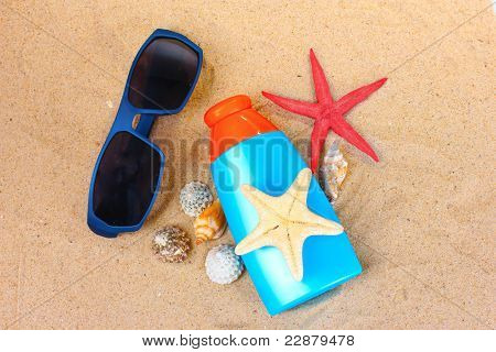 sunblock in bottle, sunglasses, shells and starfish on sand