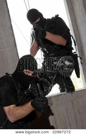 Soldados en entrar en la ventana con Rifles Ak-47 de máscaras