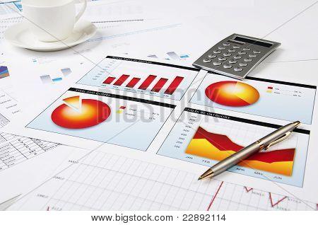 Diagramme, Taschenrechner, Kugelschreiber und Tasse Kaffee