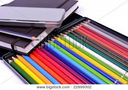 Libro de Illustrator, lápiz negro y caja de lápices de colores