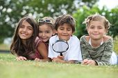 stock photo of pre-teen boy  - Kids playing with magnifying glass in park - JPG