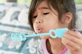 Child Blowing Bubbles Outdoors In Summer poster