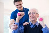 Physiotherapist Helping Denopr Man To Lift Hand Weights poster