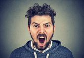 Young Bearded Man Looking At Camera And Shouting Expressively In Fury. poster
