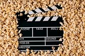 Clapper Board And Pop Corn. Black Wooden Movie Clapper With Sweet Popcorn, Close-up. Movie Time Conc poster