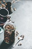 Coffee composition on dark background. Coffee beans in glass jar, coffee cups and old metallic coffe poster