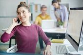 Busy young woman with smartphone talking to client by workplace with colleagues on background poster