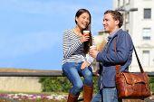Friends talking drinking coffee on lunch break outdoor in the spring sun on city street. Happy Multi poster