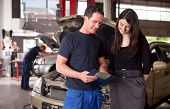 foto of auto repair shop  - A man mechanic and woman customer discussing repairs done to her vehicle - JPG