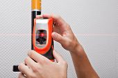 foto of gage  - Man hands measuring with laser level gage - JPG