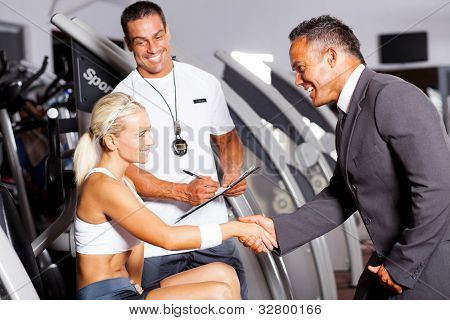 friendly gym manager greeting customer