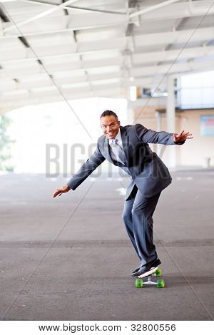 happy young businessman on skateboard