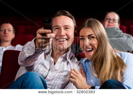 Couple and other people, probably friends, in cinema watching a movie, they try to switch to another program that is not possible in a cinema