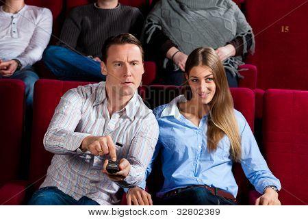 Paar und anderen Menschen, wahrscheinlich Freunde im Kino einen Film aufpassend, versuchen sie, zu einer anderen wechseln
