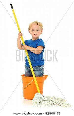 Bela loira criança menino pé no balde faxina sobre branco