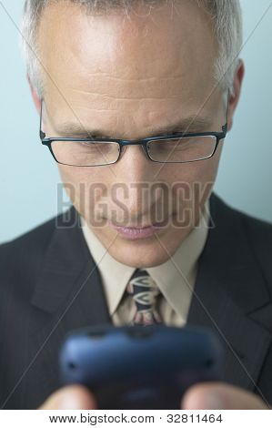 Middle-aged businessman looking at cell phone