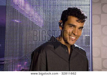 Portrait of Hispanic man wearing hands free device