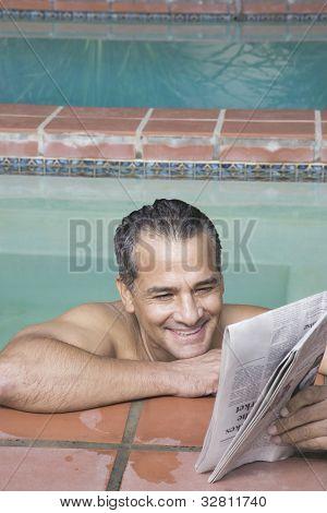 Hispanic man reading newspaper in swimming pool