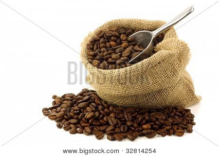 coffee beans in a burlap bag with an aluminum scoop on a white background
