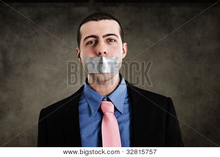 Portrait of a businessman having the mouth closed with tape