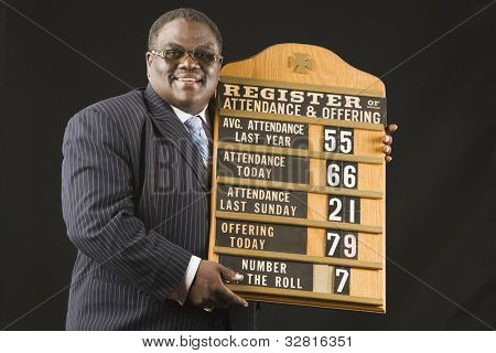 African man holding hymn board