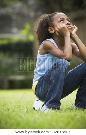 African girl sitting on soccer ball