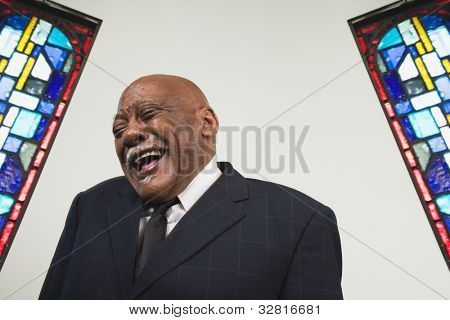 Senior African man laughing in church