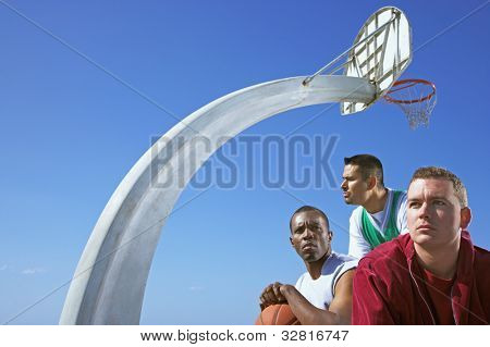 Multi-ethnic men under basketball hoop