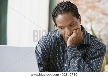 Afrikanische Man looking at laptop