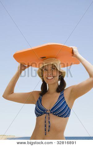 Woman holding boogie board on head