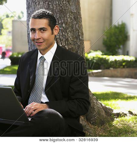 Hispanic businessman typing on laptop under tree