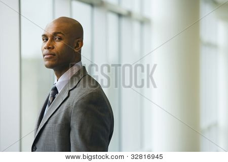African businessman standing next to window