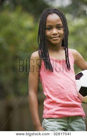 African girl holding soccer ball