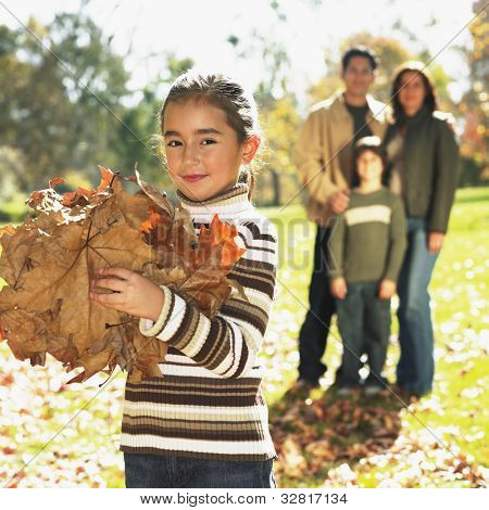 Mixed Race girl playing in autumn leaves