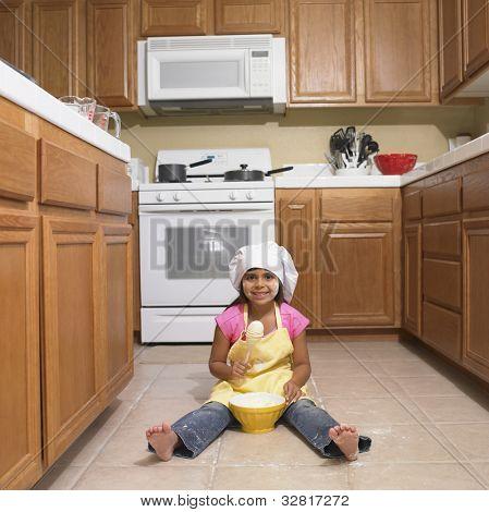 Hispanic girl mixing bowl on kitchen floor