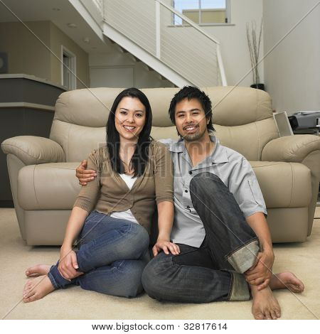 Multi-ethnic couple sitting on floor