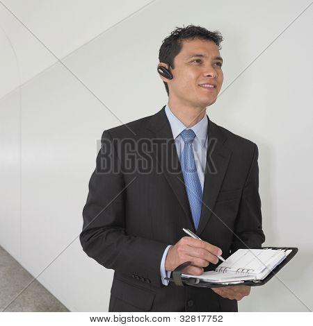 Mixed Race businessman writing in date book